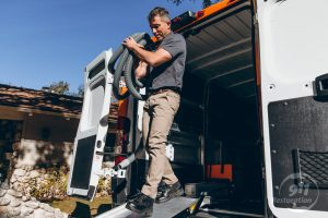 sewage removal technician carrying equipment out of van